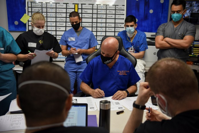"""Varon and his team go over patient files during a daily meeting. """"I'm afraid that at some point in time I'm going have to make some very serious decisions,"""" Varon said in July. """"I'm starting to get the idea that I cannot save everybody."""""""