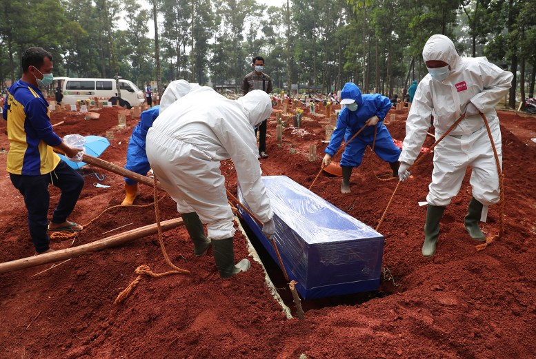 Workers in protective gear lower a coffin of a Covid-19 victim to a grave for burial at the Cipenjo Cemetery in Bogor, West Java, Indonesia, on Wednesday, July 14.