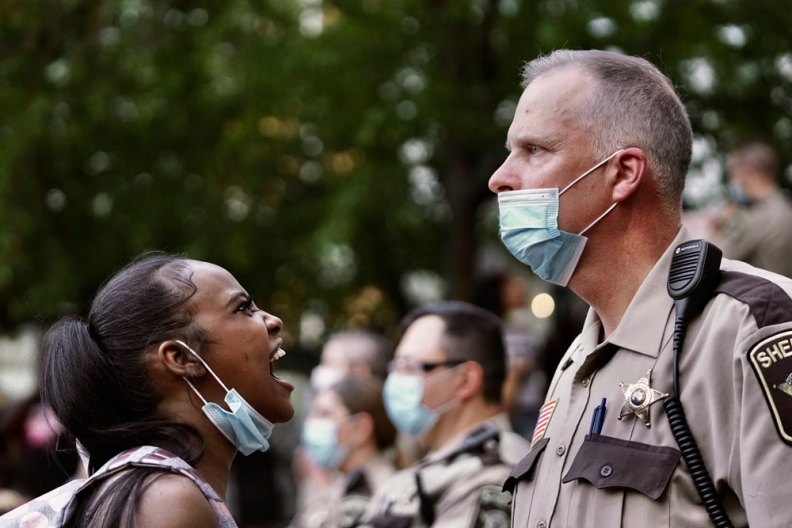 A woman yells at a sheriff's deputy during a protest following the death of George Floyd at the hand of Minneapolis police officers, on Thursday, May 28 in Minneapolis.