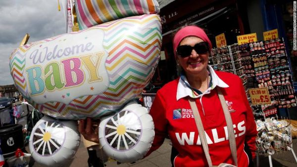 Royal super fan Anne Daley poses with baby-themed balloons as she waits near Windsor Castle, west of London on Monday.