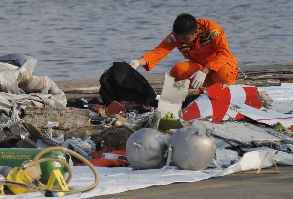 A member of Indonesian Search and Rescue Agency (Basarnas) inspects debris believed to be from the Lion Air passenger jet. (Photo by Tatan Syuflana/AP Photo)