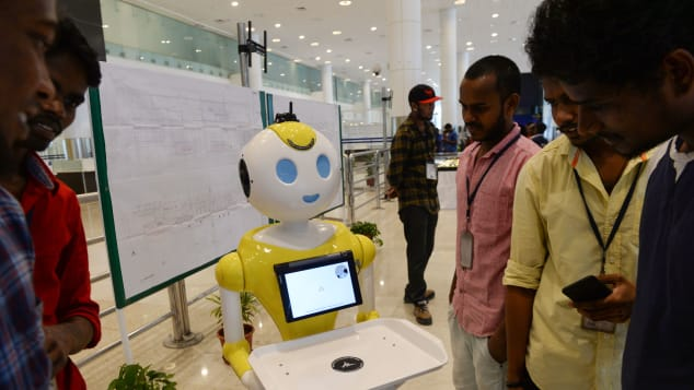 Staff check out one of the humanoid robots in the arrival hall of Chennai International Airport.
