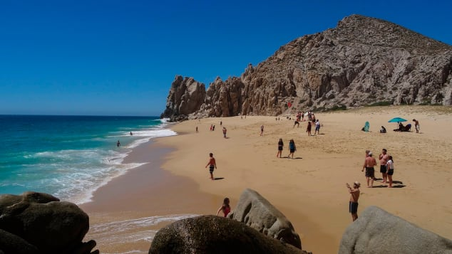 """Tourists sunbathe at the """"Love Beach"""" in Los Cabos, Baja California Sur state, Mexico in March, 2018."""