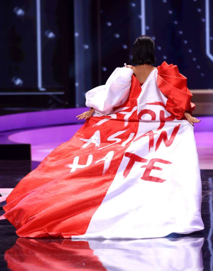"""Miss Universe Singapore Bernadette Belle Ong wears a Arwin Meriales x Paulo Pilapil Espinosa cape hand-painted with the hashtag """"#StopAsianHate."""""""