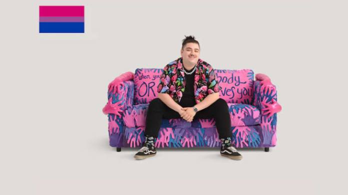 """Spoken word poet Brian Lanigan pictured on IKEA's """"bisexual"""" couch, which was inspired by his work."""