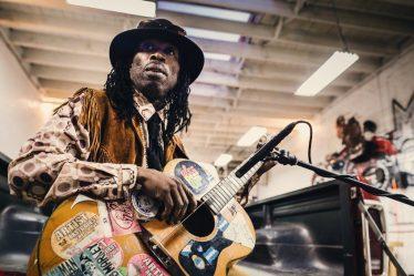 Il se nomme Brushy One String (One string = une corde), il est guitariste/chanteur et il vient de Jamaïque. Il s'est fait connaitre lorsque un certain Luciano Blotta a réalisé un documentaire sur la musique underground jamaïcain « Rise Up ».