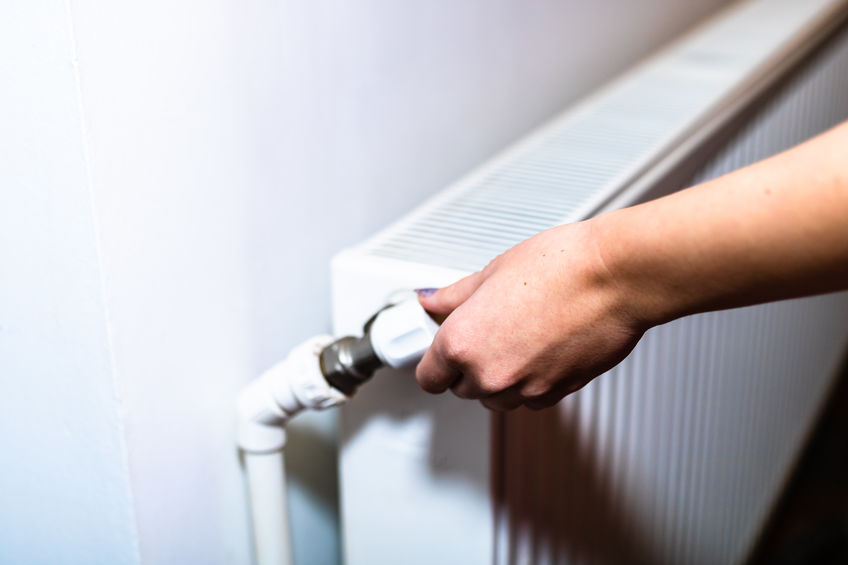 Close up of hand adjusting heating thermostat. Central heating concept