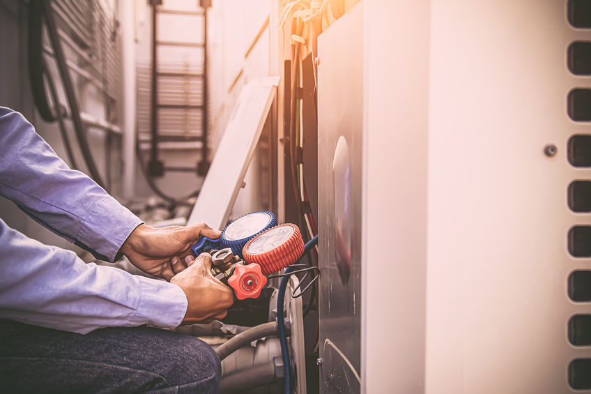 man checking the pressure on a boiler
