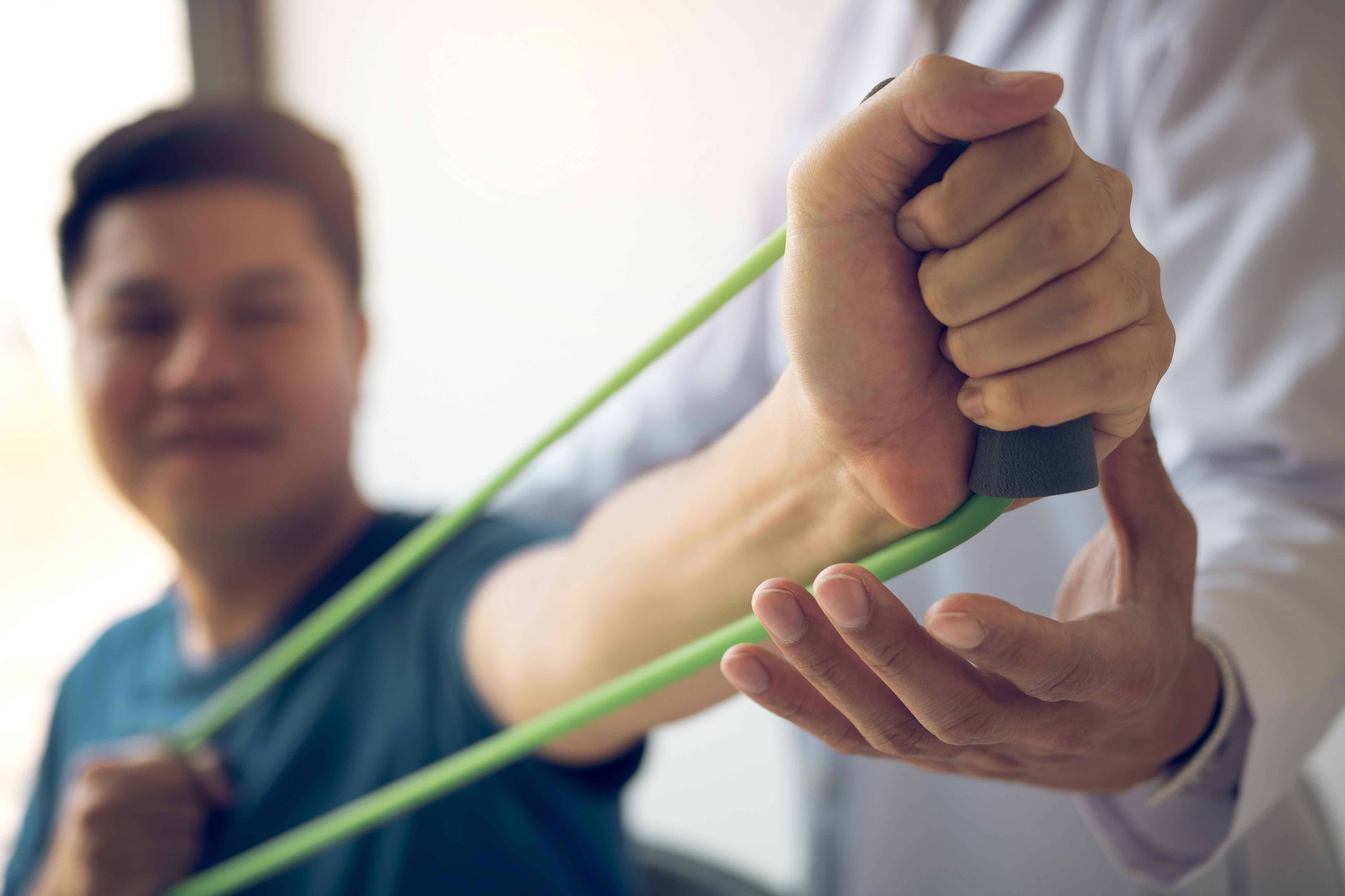 man doing rubber band exercise with Physical therapist
