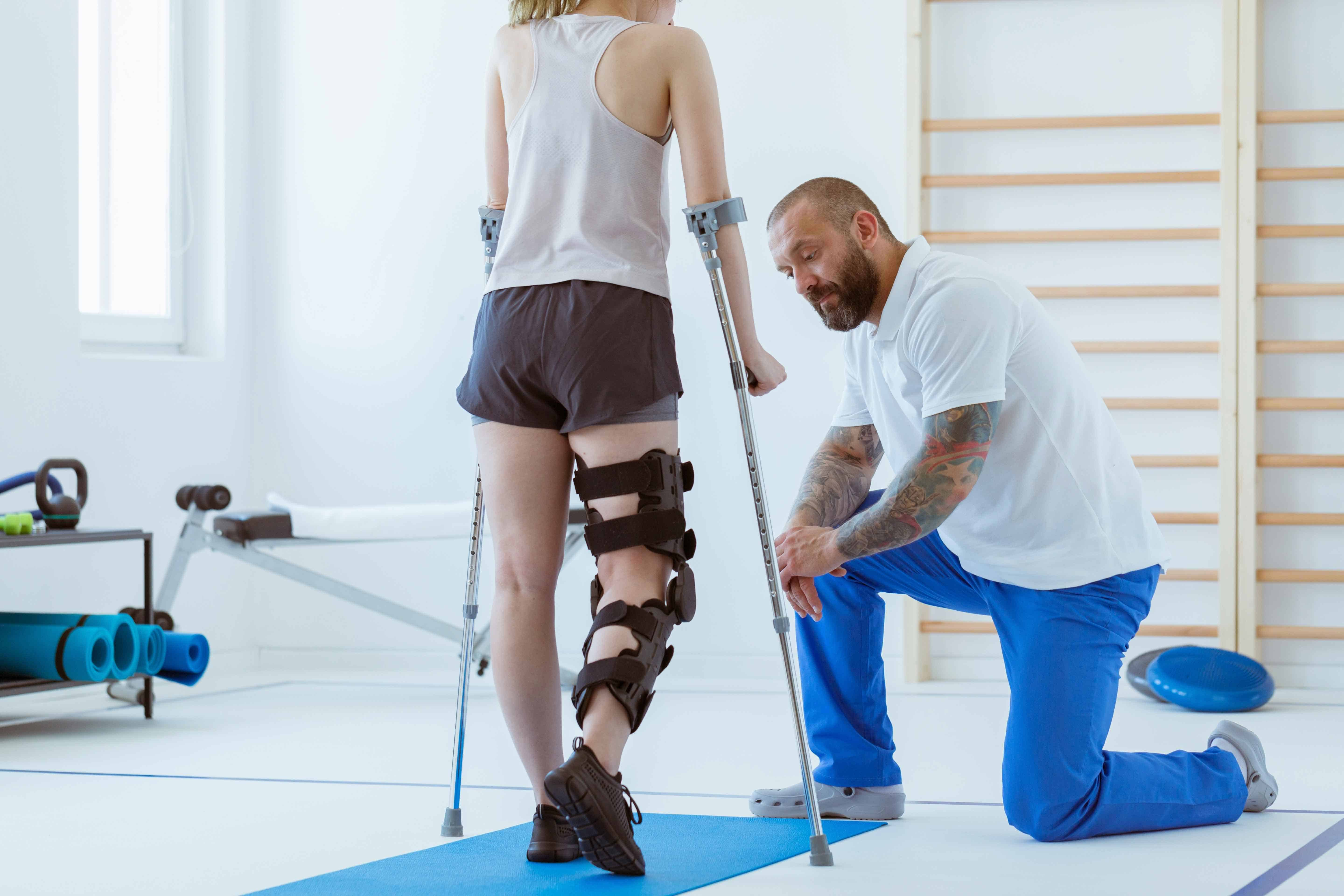 Physical therapist fitting patient with crutches