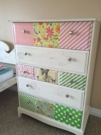 Raised stencil on two drawers, tissue paper and napkins on others.