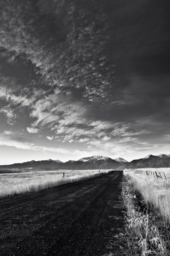 A gravel road leads to the Wallowa Mountains in early morning light.