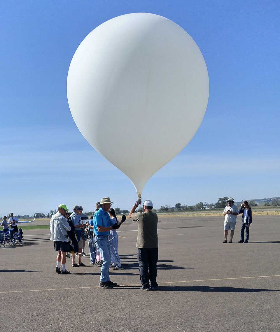 Weather balloons are big. This one was seven feet tall once filled with enough gas to lift its 12 pound science payload. Over half a dozen volunteers, visiting the airport to watch the eclipse, helped get this flight underway.
