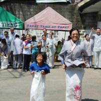 """東禪佛教學院學生與貧民窟孩子們一同挑戰""""跳麻袋""""遊戲。菲律賓小孩們的天真與活力很快就与同學們打成一片,就算挺着大太阳,大家都还是玩得不亦樂乎,增進了彼此的感情。"""