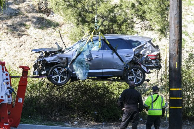 """FILE - In this Feb. 23, 2021, file photo, a crane is used to lift a vehicle following a rollover accident involving golfer Tiger Woods, in the Rancho Palos Verdes suburb of Los Angeles. Detectives are looking at data from the so-called """"black box"""" of Tiger Woods' SUV to get a clearer picture of what occurred during the Southern California rollover crash last week that seriously injured the golf star, authorities said Wednesday, March 3. (AP Photo/Ringo H.W. Chiu, File)"""