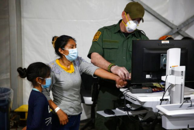 A migrant and her daughter have their biometric data entered at the intake area of the Donna Department of Homeland Security holding facility, the main detention center for unaccompanied children in the Rio Grande Valley, in Donna, Texas, Tuesday, March 30, 2021. (AP Photo/Dario Lopez-Mills, Pool)