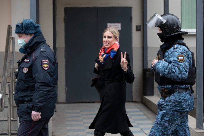 Russian opposition activist Lyubov Sobol, center, gestures as she walks to the court escorted by police and Russian Federal Bailiffs service officers in Moscow, Russia, Monday April 5, 2021. A Moscow court will start considering the case against Navalny ally Lyubov Sobol, who is charged with unlawful entry into a dwelling. In December Sobol rang the doorbell of a flat of a relative of an alleged FSB agent Konstantin Kudryavtsev, whom Navalny accused of his poisoning. (AP Photo/Pavel Golovkin)