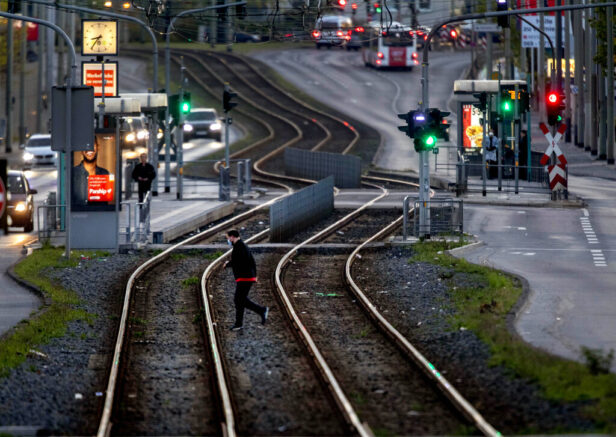 A man crosses tram rails in Frankfurt, Germany, before curfew on Saturday, April 24, 2021. From the weekend on a curfew becomes effective to avoid the outspread of the coronavirus. (AP Photo/Michael Probst)