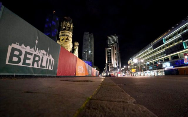 The deserted 'Budapesater Strasse' (Budapest Road) at the bottom of the Kaiser Wilhelm Memorial Church, left, is pictured during a nationwide curfew in Berlin, Germany, Saturday, April 24, 2021. To reduce the number of coronavirus infections, people in Germany are not allowed to be outdoors between ten o'clock in the night and five o'clock in the morning. (AP Photo/Michael Sohn)