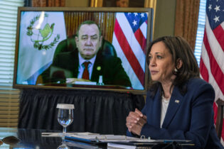 Vice President Kamala Harris meets virtually with Guatemala's President Alejandro Giammattei, seen on screen at left, Monday, April 26, 2021, from her ceremonial office at the Eisenhower Executive Office Building on the White House complex in Washington. (AP Photo/Jacquelyn Martin)