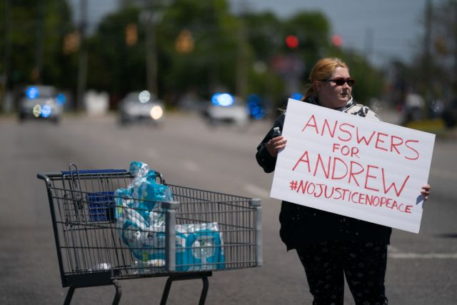 ELIZABETH CITY, NC - APRIL 23: Robin Woodard holds a sign while blocking an intersection during a protest march April 23, 2021 in Elizabeth City, North Carolina. Protestors were calling for the release of body camera footage from the shooting death of Andrew Brown Jr. on April 21. (Photo by Sean Rayford/Getty Images)