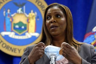 New York Attorney General Letitia James removes her mask at the beginning of a news conference at her office, in New York, Friday, May 21, 2021. James said Friday that she's assigned two lawyers to work with the Manhattan district's attorney's office on a criminal investigation into former President Donald Trump's business dealings. (AP Photo/Richard Drew)