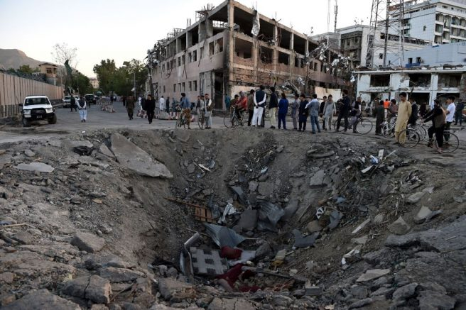 TOPSHOT - Afghan security forces and residents stand near the crater left by a truck bomb attack in Kabul on May 31, 2017. - At least 80 people were killed and hundreds wounded May 31 when a massive truck bomb ripped through Kabul's diplomatic quarter, bringing carnage to the streets of the Afghan capital and shattering windows hundreds of metres away. (Photo by WAKIL KOHSAR / AFP) (Photo by WAKIL KOHSAR/AFP via Getty Images)