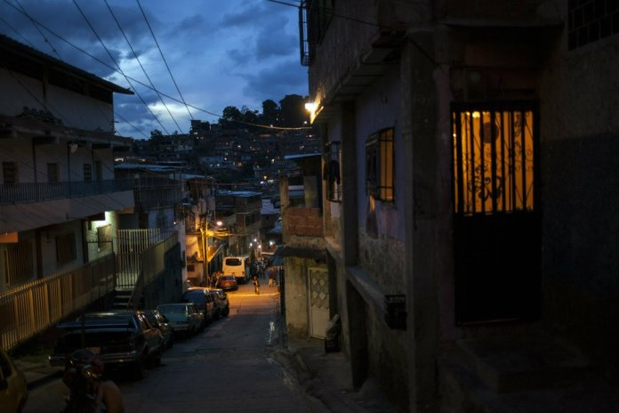 A street goes dark as the sun sets in the Petare slum of Caracas, Venezuela. When night falls, streets in Caracas clear as most residents abide by an undeclared curfew out of fear for their safety. (AP Photo/Rodrigo Abd)