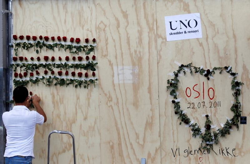 FILE PHOTO: A man arranges flowers next to a graffitti marking a bomb attack last Friday in the centre of Oslo