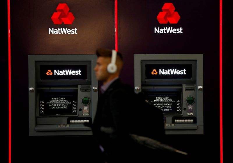 FILE PHOTO: A man walks past ATM machines at branch of the NatWest bank in Manchester
