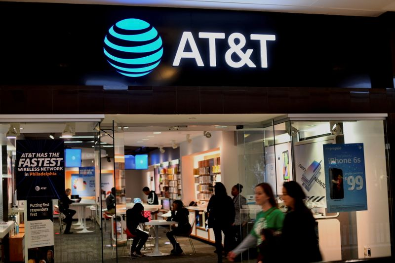 FILE PHOTO: Shoppers walk past an AT&T store at the King of Prussia Mall in King of Prussia