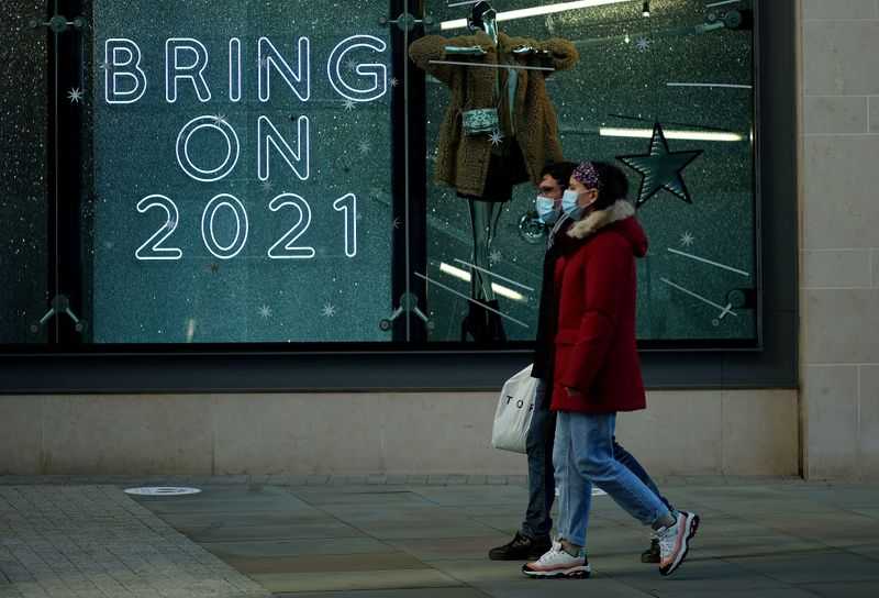 FILE PHOTO: People walk past a sign in a shop window amid the outbreak of the coronavirus disease (COVID-19) in Manchester, Britain