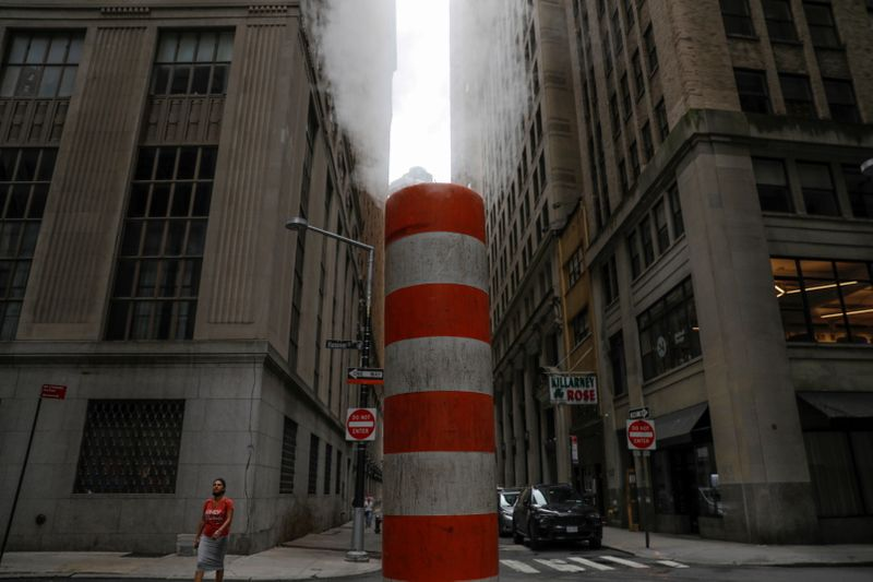 FILE PHOTO: A person walks by a steam pipe in the Financial District after The United Nations released the Intergovernmental Panel on Climate Change's (IPCC) latest report, in Manhattan, New York City