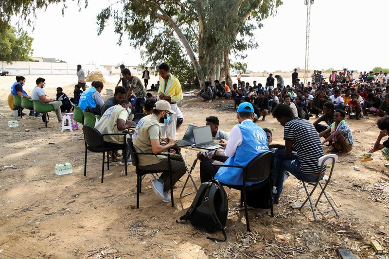 Migrants gather at a detention center in Tripoli