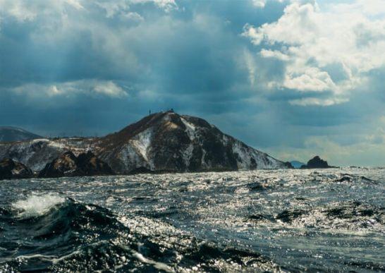 荒波の津軽海峡から眺める龍飛岬(2014年3月)/撮影・小林廉宜