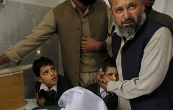 A Pakistani man comforts a student standing at the bedside of a boy who was injured in a Taliban attack on a school, at a local hospital in Peshawar, Pakistan, Tuesday, Dec. 16, 2014. Taliban gunmen stormed a military-run school in the northwestern Pakistani city of Peshawar on Tuesday, killing and wounding scores, officials said, in the worst attack to hit the country in over a year.(AP Photo/Mohammad Sajjad)
