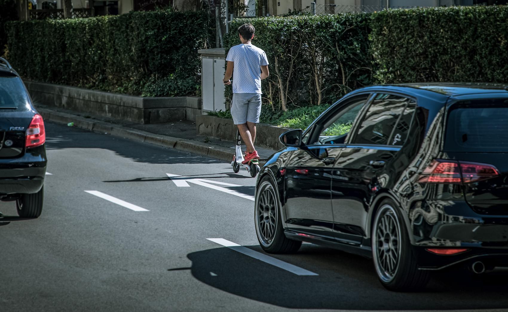 Un usager de la trottinette électrique sur une voie réservée aux voitures à Zurich. (Philippe Rossier)