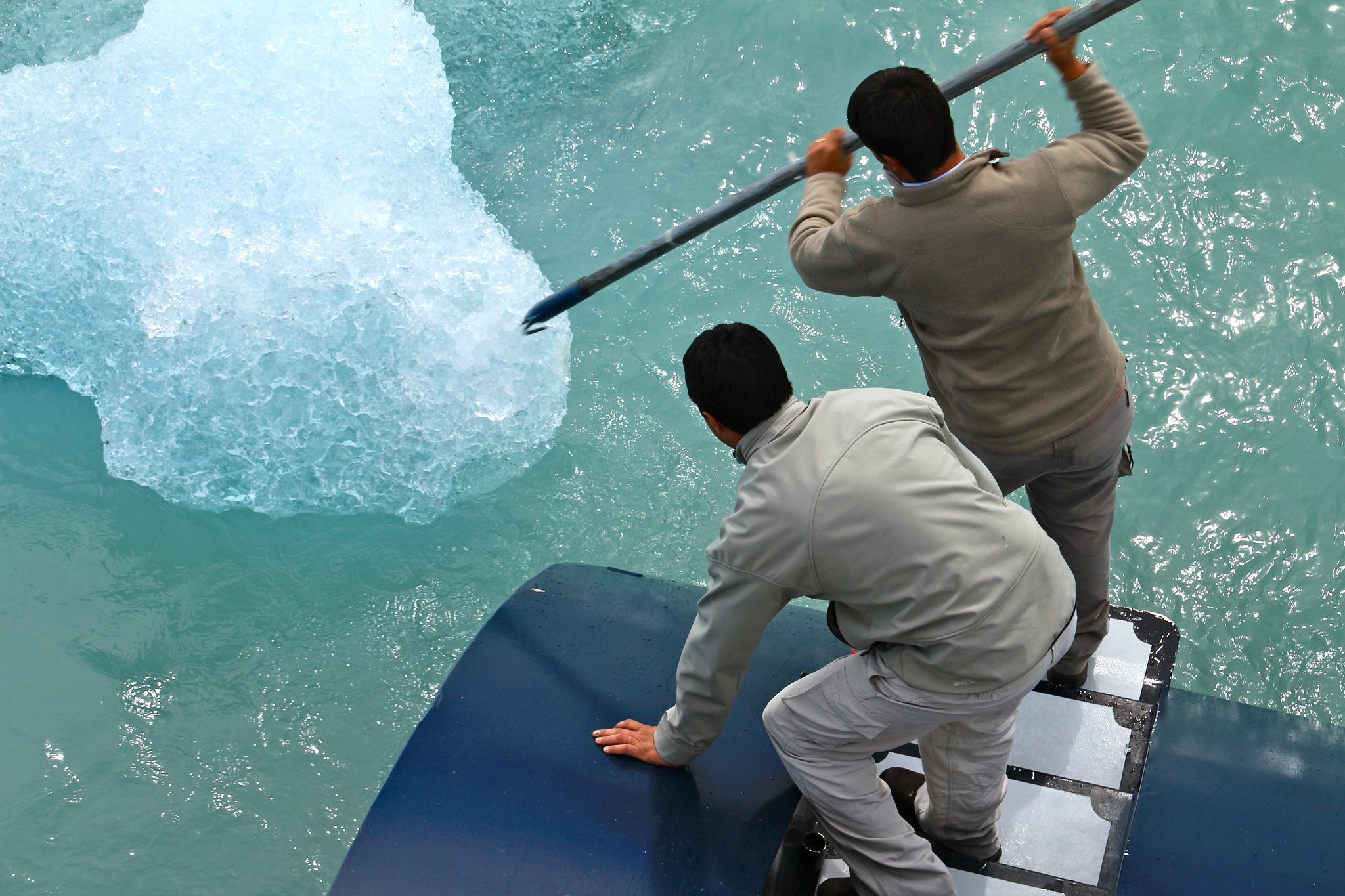two men breaking up a glacier with a long instrument