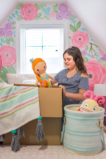 a girl packing up her toys into a box in her bedroom