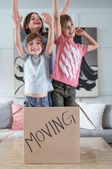 three children standing inside a moving box