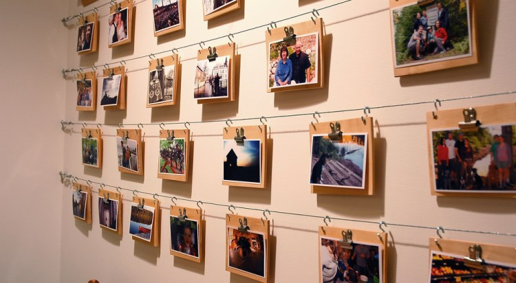a gallery wall of photos hung on a wire