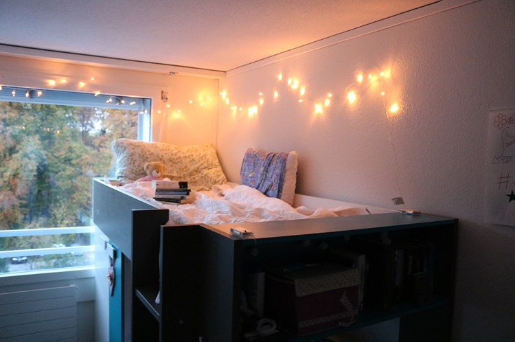 a dorm room with a string of lights hung along the window and wall