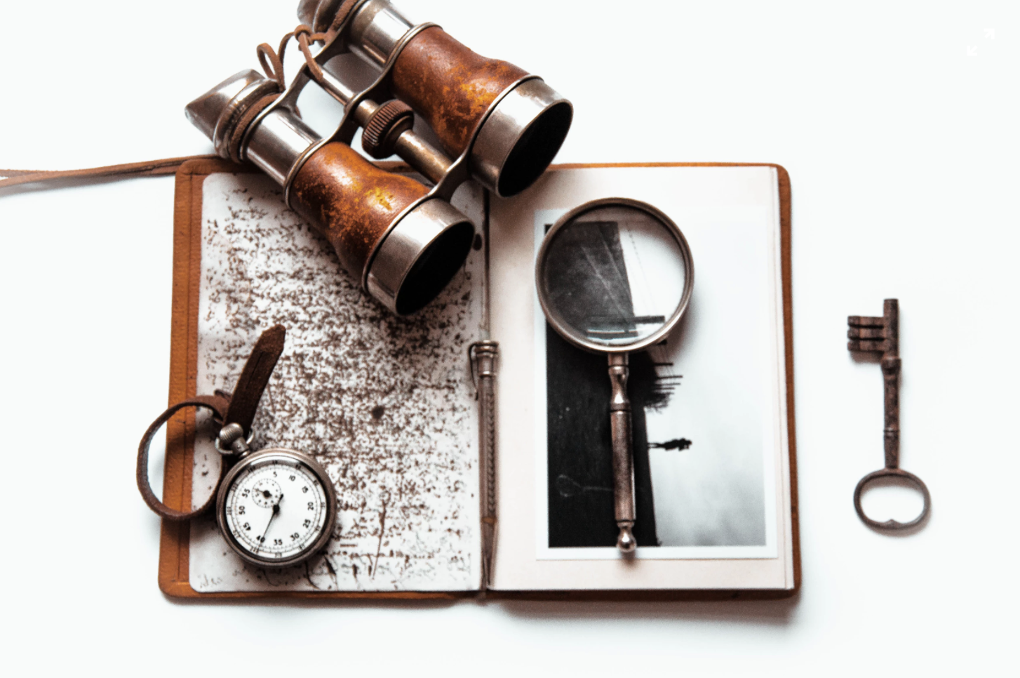 binoculars, a compass, a magnifying glass, and old key and a notebook
