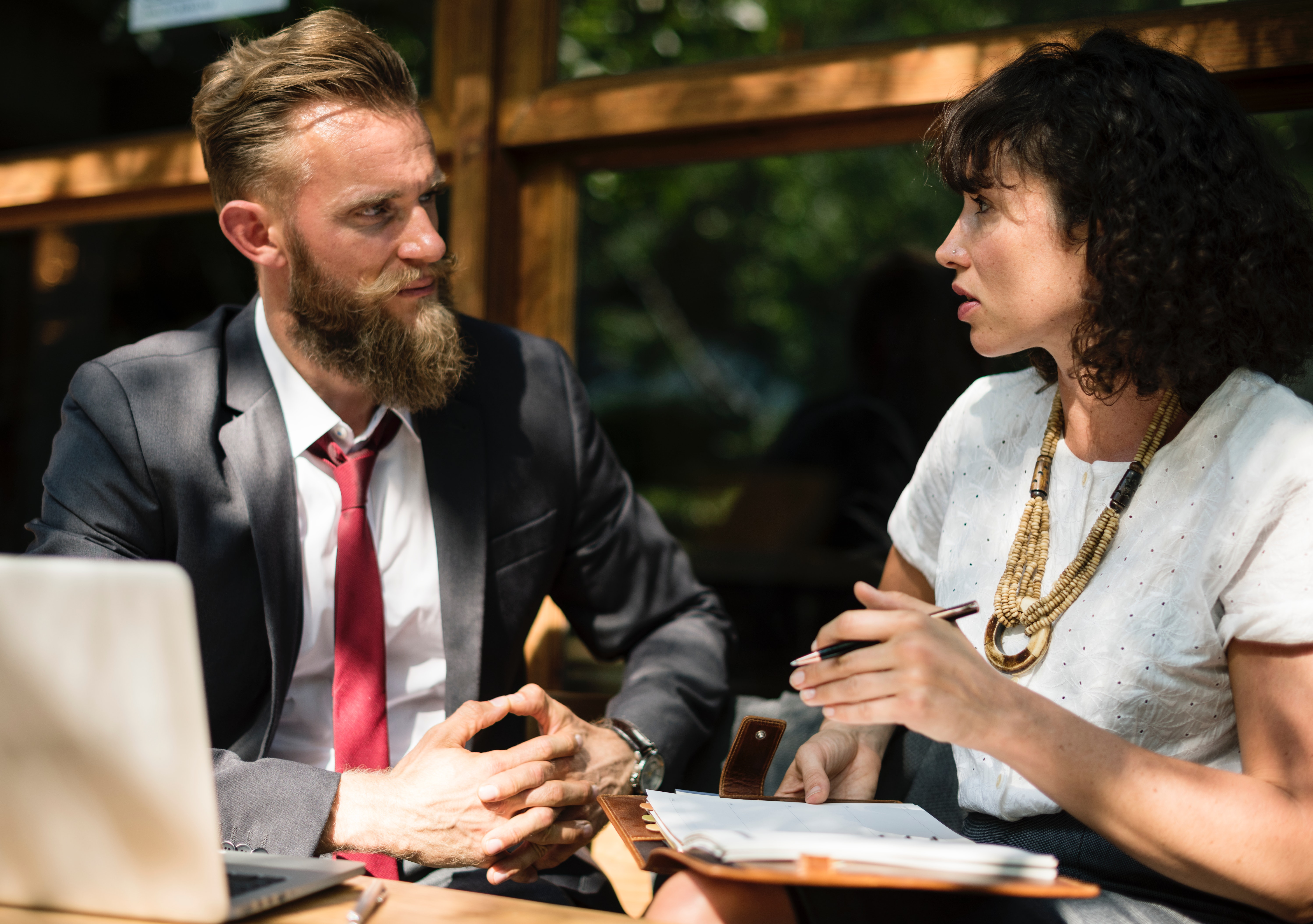 a man and woman having a meeting outdoors