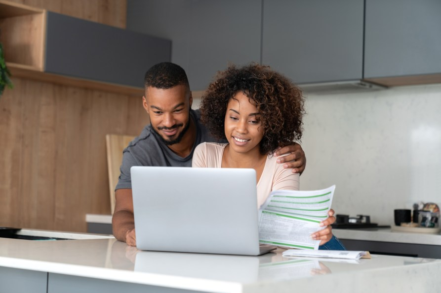 A couple paying bills online at home using a laptop computer