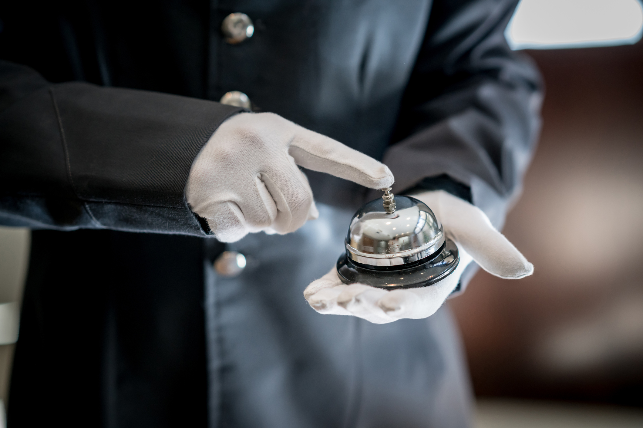 A bell boy at a hotel ringing the bell using white gloves