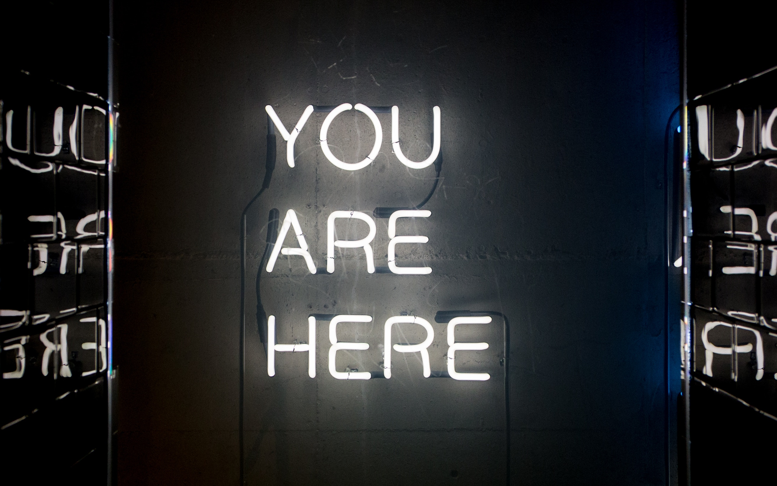 a neon sign on a wall with the words; YOU ARE HERE