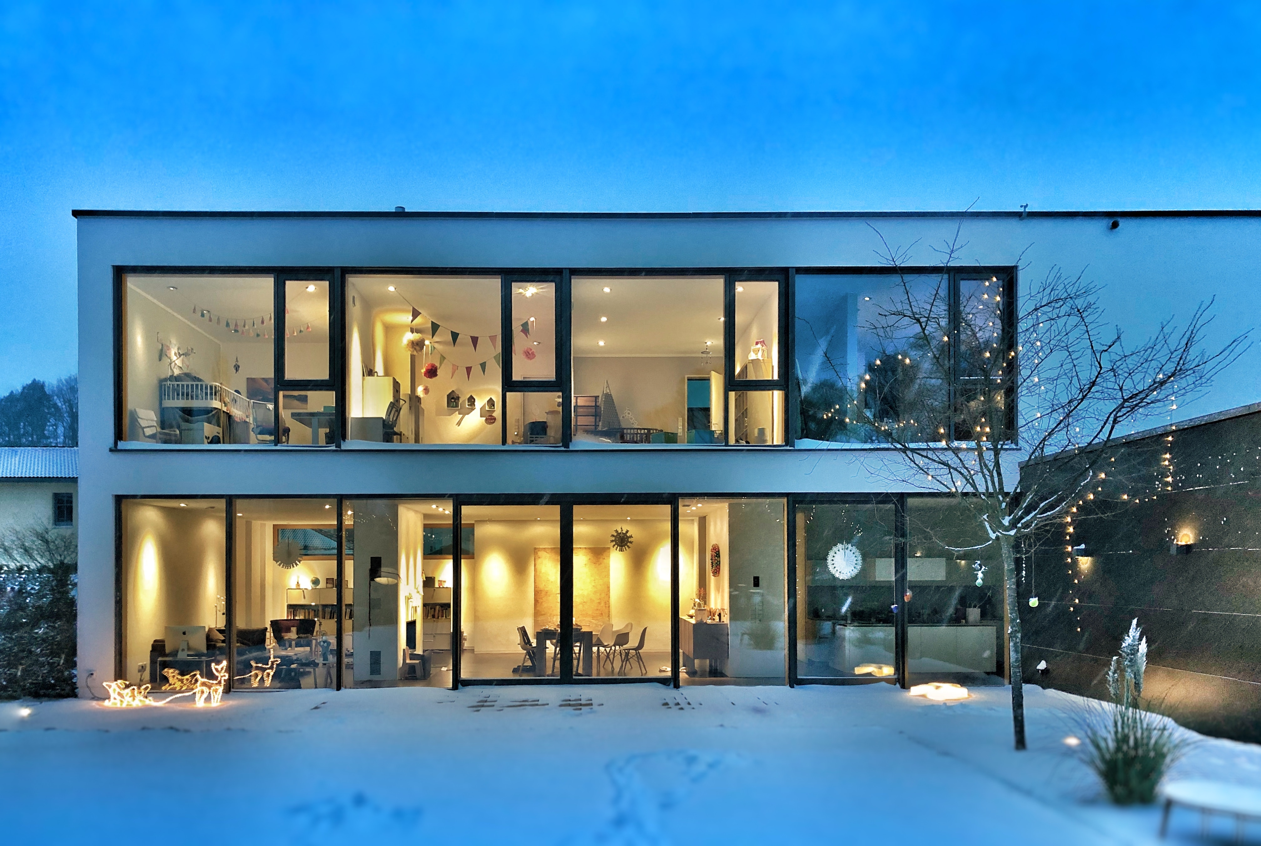 a two-storey home with big glass walls exposed to the backyard