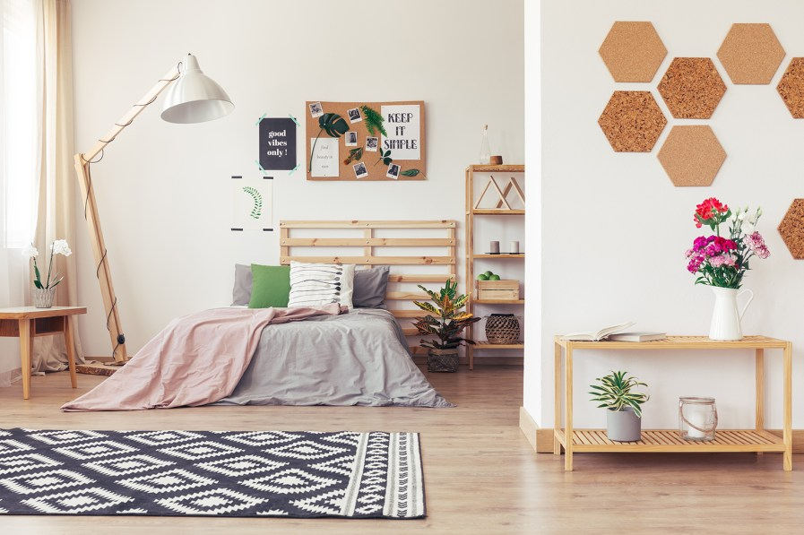 a bedroom with lots of wooden furniture and indoor plants