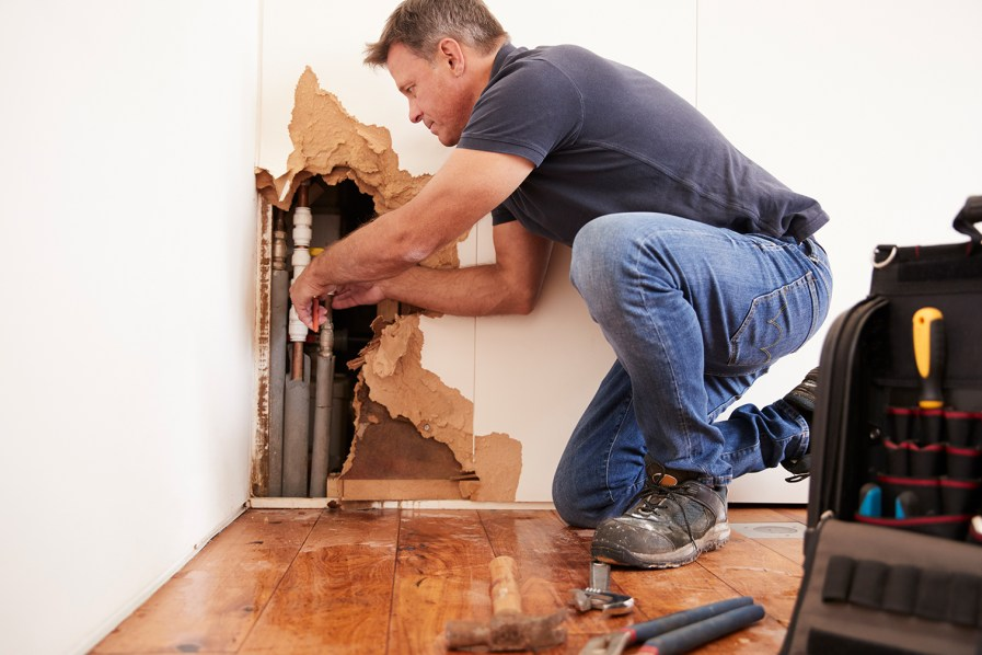 a plumber fixing pipes within a wall